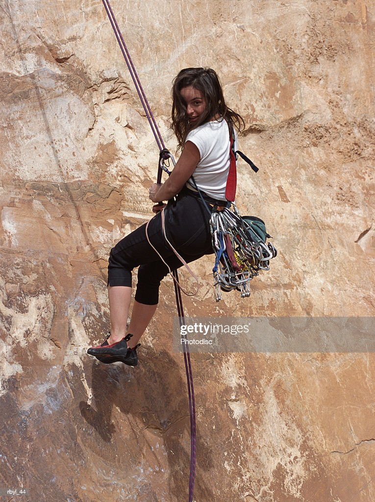 a young woman is decinding from completing a climb up the face of a rock cliff wall : Foto de stock