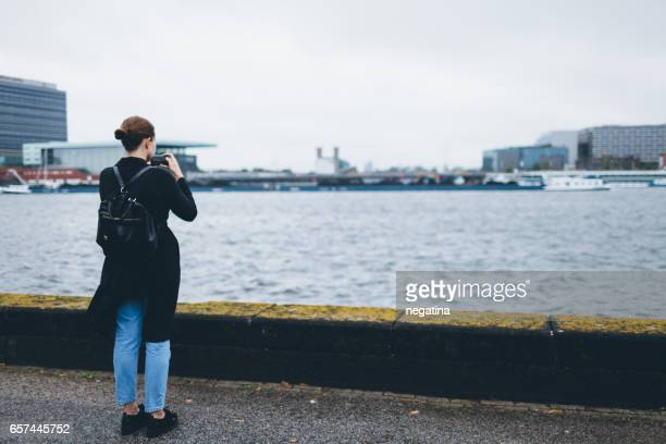 a young woman making pictures on her smartphone in front of IJ river in Amsterdam, Netherlands
