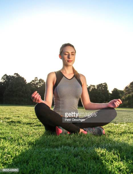 a Young woman meditating outdoors.