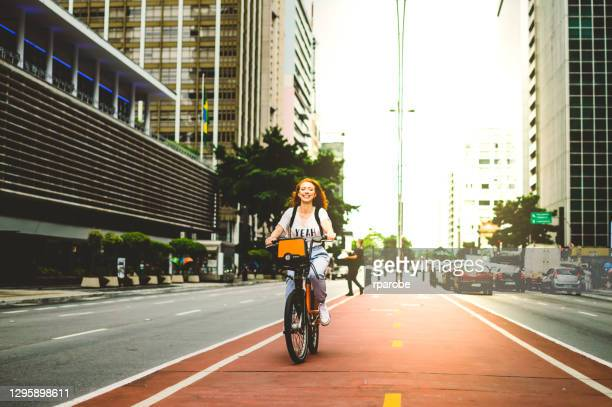 a young woman smiling while riding a bicycle, down paulista avenue - brazil stock pictures, royalty-free photos & images