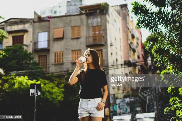 ポルト・アレグレでコーヒーを飲みながら町を歩き回る若い女性 - ポルトアレグレ ストックフォトと画像