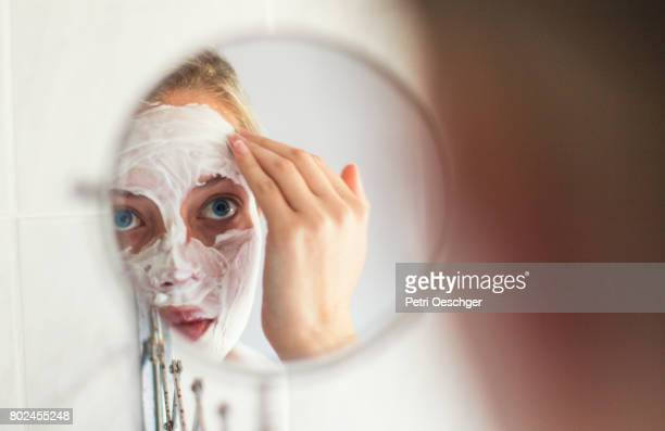 a Young woman with blue eyes applying a beauty mask.