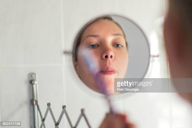 a Young woman with blue eyes brushing her teeth while looking in the mirror.