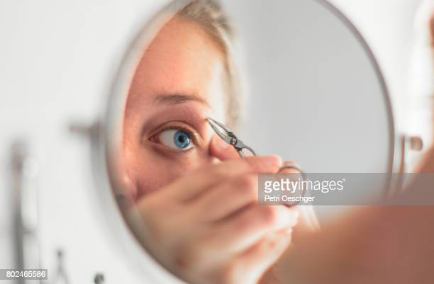 a young woman with blue eyes plucking her eyebrows. - 修眉 個照片及圖片檔