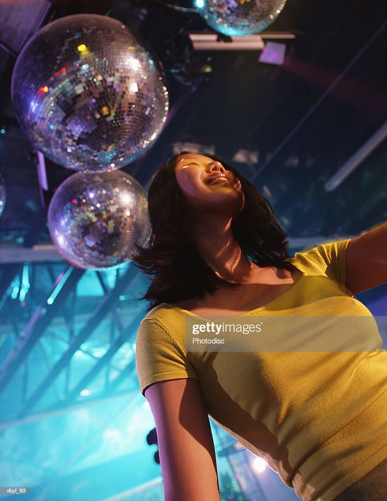 a young woman with long black hair dressed in a yellow shirt is dancing in a nightclub : Foto de stock