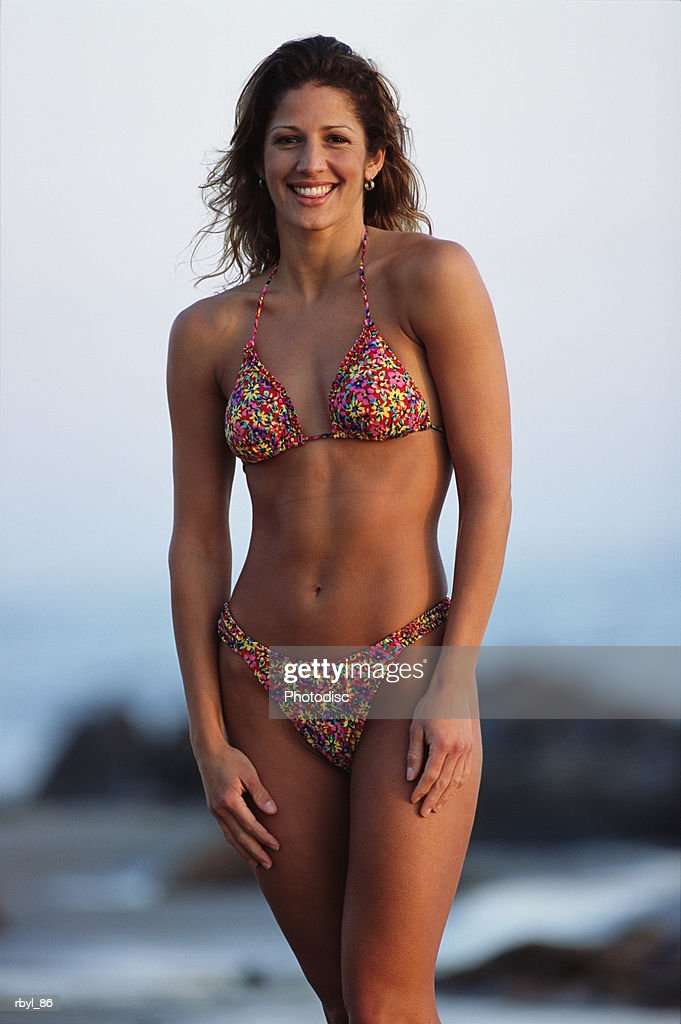 a young woman with long brown hair in a flowered bikini is standing on the beach with the rocky shore and ocean in the background : Foto de stock