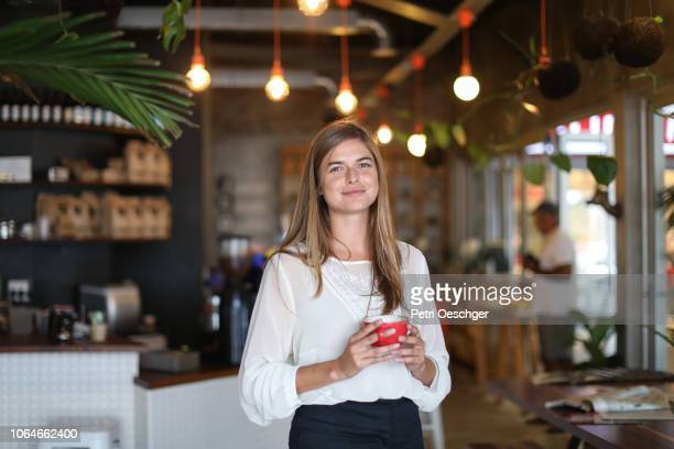 a young woman working in a cafe. - restaurant manager stock pictures, royalty-free photos & images