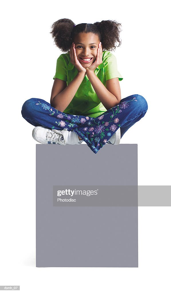 a younng african american girl in jeans and a green shirt sits with her legs crossed atop a blank sign : Stock Photo