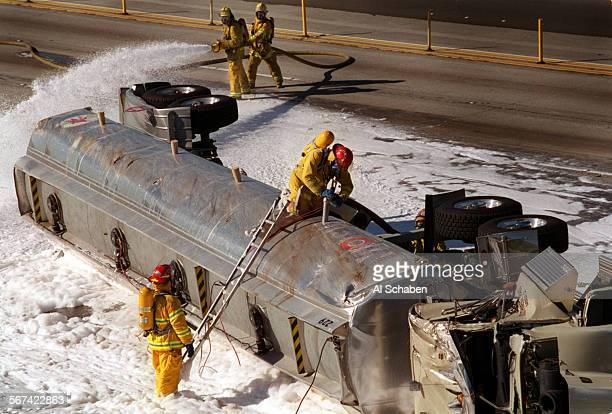 AA91bigrigcrash21220AS––ANAHEIM––An Anaheim fire captain drains gasoline from a tractor trailer that overturned early Saturday morning on the...