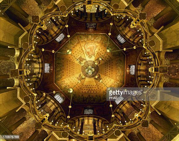 Aachen Cathedral Palatine Chapel Lowangle shot of the bronze Barbarossa's Chandelier and the vault of the Octagon with golden mosaics depicting...