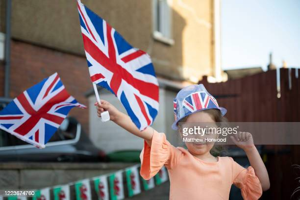 Aaliyah Omar waves a union jack flag at a VE Day street party on May 08 2020 in Cardiff United Kingdom The UK commemorates the 75th Anniversary of...