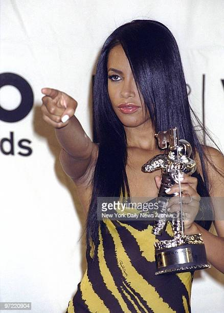 Aaliyah points to the crowd while brandishing her award for Best Female Video backstage at the 2000 MTV Music Awards