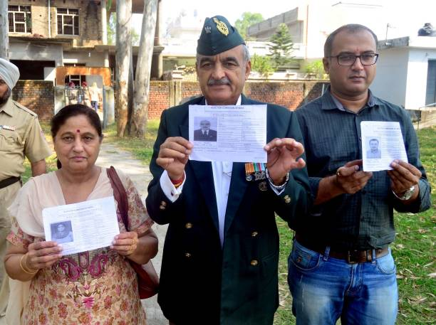 Aam Aadmi Party candidate Maj Gen Suresh Khajuria along with his wife Tripta Khajuria and son Rohit shows voter card after casting the vote outside...