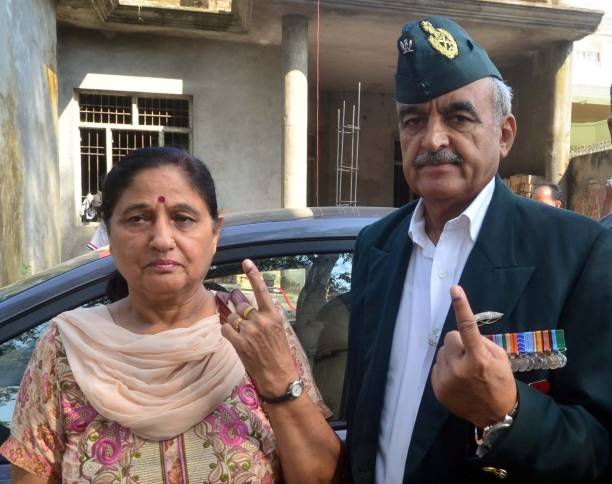 Aam Aadmi Party candidate Maj Gen Suresh Khajuria along with his wife Tripta Khajuria and son Rohit shows her ink mark after casting the vote outside.