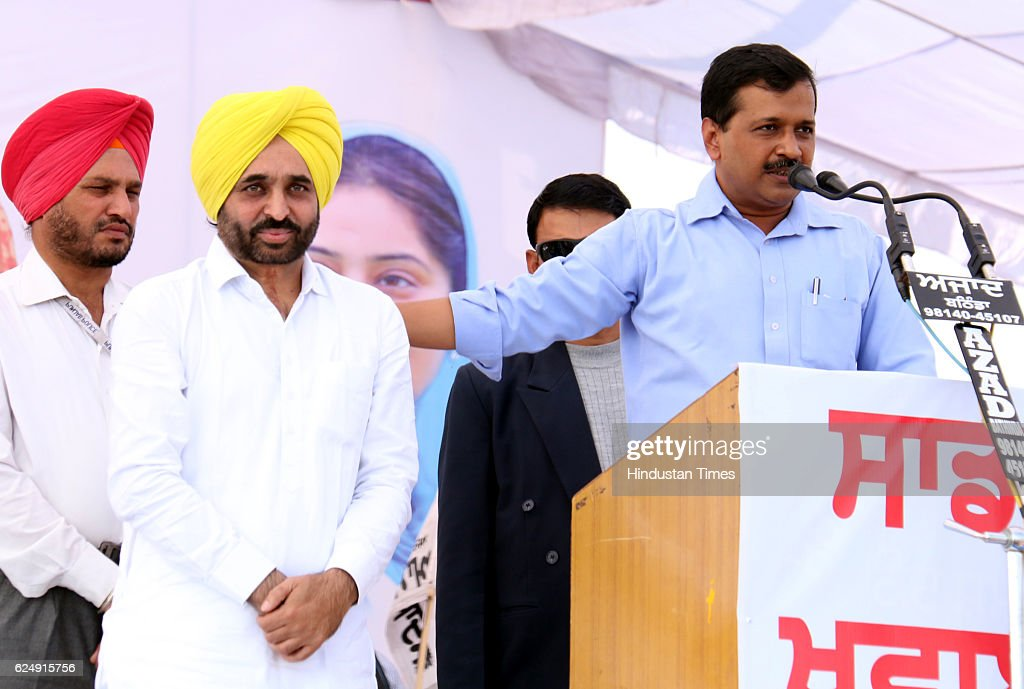 Aam Aadmi Party Chief and Delhi Chief Minister Arvind Kejriwal patting back of Aam Aadmi Party Sangrur MP Bhagwant Mann during a rally at Kotshamir...