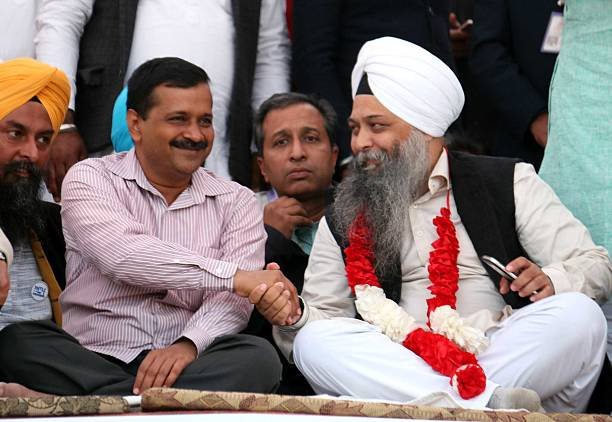 Aam Aadmi Party Convener and Chief Minister of Delhi Arvind Kejriwal handshakes with MLA Jarnail Singh during a rally at Kolianwali village of Lambi..