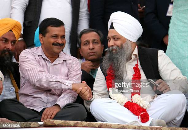 Aam Aadmi Party Convener and Chief Minister of Delhi Arvind Kejriwal handshakes with MLA Jarnail Singh during a rally at Kolianwali village of Lambi...