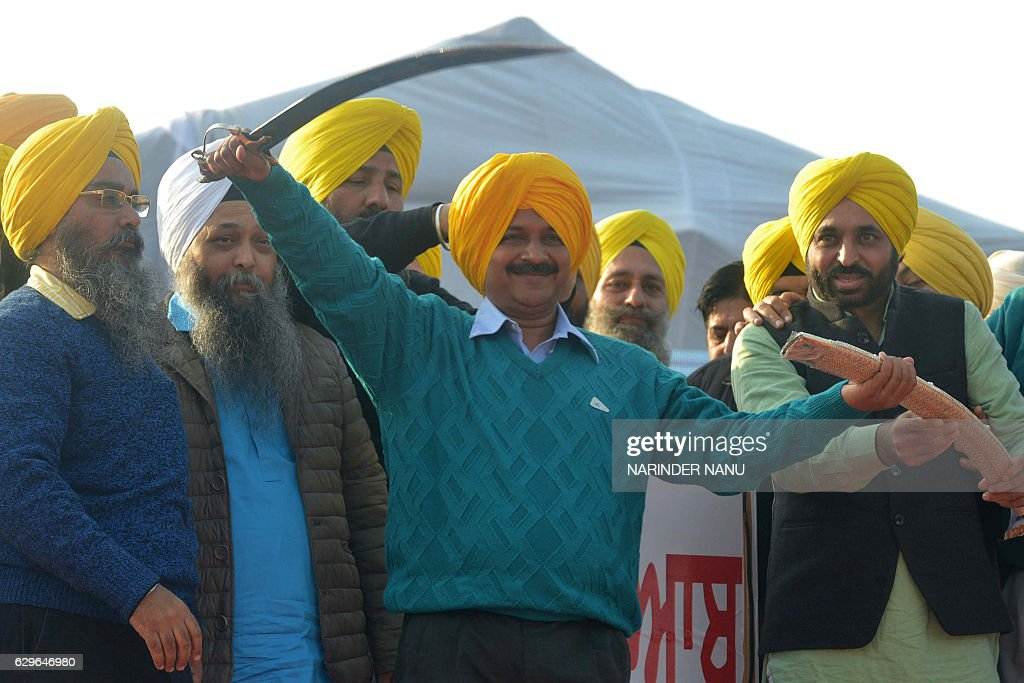 Aam Aadmi Party leader and Chief Minister of Delhi Arvind Kejriwal holds a sword presented by Aam Aadmi Party leader Jaswinder Singh and AAP Member...