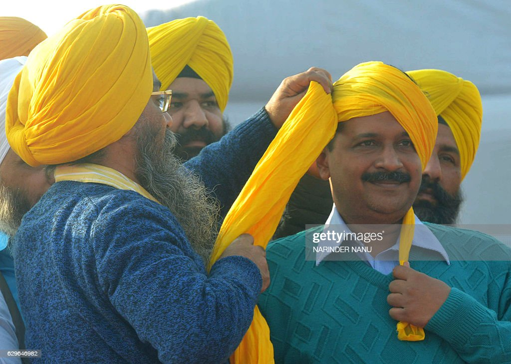 Aam Aadmi Party leader Jaswinder Singh ties a turban onto AAP leader and Chief Minister of Delhi Arvind Kejriwal during an AAP rally in Majitha some..
