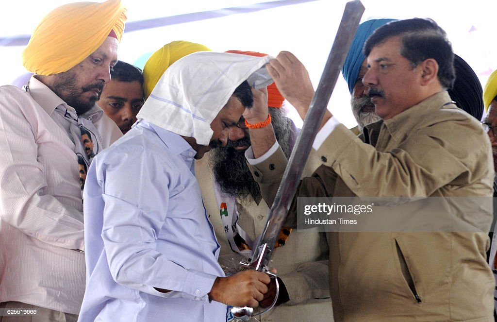 Aam Aadmi Party leader Sanjay helping in wearing a head gear to Delhi Chief Minister Arvind Kejriwal during a rally at Samana on November 24 2016 in..