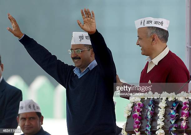 Aam Aadmi Party president Arvind Kejriwal greets his supporters as fellow Minister Manish Sisodia congratulates him during his swearing-in ceremony...