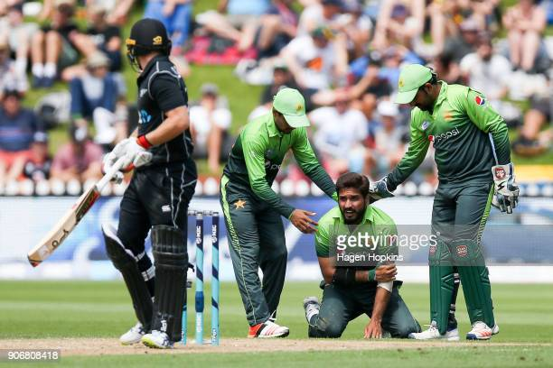 Aamer Yamin and Sarfraz Ahmed of Pakistan check on the health of Rumman Raees during game five of the One Day International Series between New...