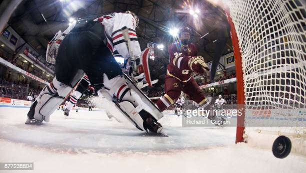 Aapeli Räsänen of the Boston College Eagles swings at the puck before it enters the net on a goal by teammate Jesper Mattila behind Cayden Primeau of...