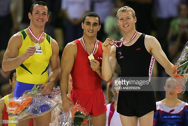 Gold medalist Marian Dragulescu of Romania silver medalist Diego Hypolito of Brazil and bronze medalist Kyle Shewfelt of Canada pose at the medal...