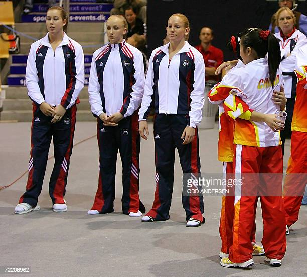 US gymnasts Natasha Kelley Anastasia Liukin and Ashley Priess looks dejected as Chinese athletes embrace during the women's team final at the Arena...