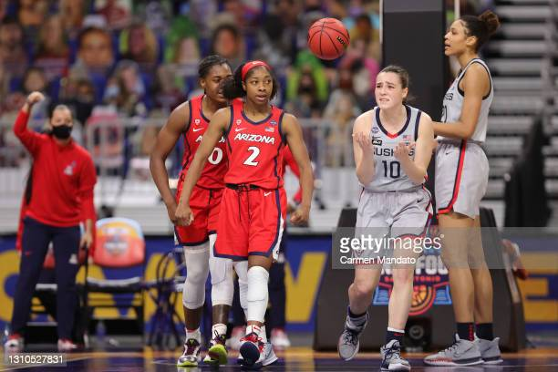 Aari McDonald of the Arizona Wildcats and Nika Muhl of the UConn Huskies react to a foul during the third quarter in the Final Four semifinal game of...