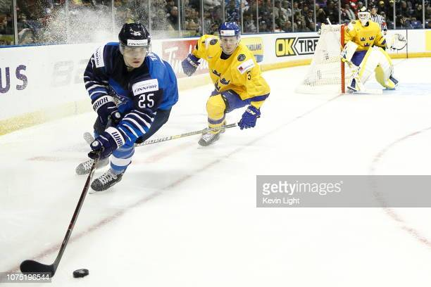 Aarne Talvitie of Finland skates with the puck while being chased by Adam Boqvist of Sweden at the IIHF World Junior Championships at the SaveonFoods...