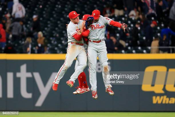 Aaron Altherr Odubel Herrera and Rhys Hoskins of the Philadelphia Phillies celebrate beating the Atlanta Braves in eleven innings at SunTrust Park on...