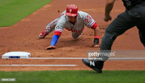 Aaron Altherr of the Philadelphia Phillies dives back safely to first base against the Texas Rangers during the first inning at Globe Life Park in...
