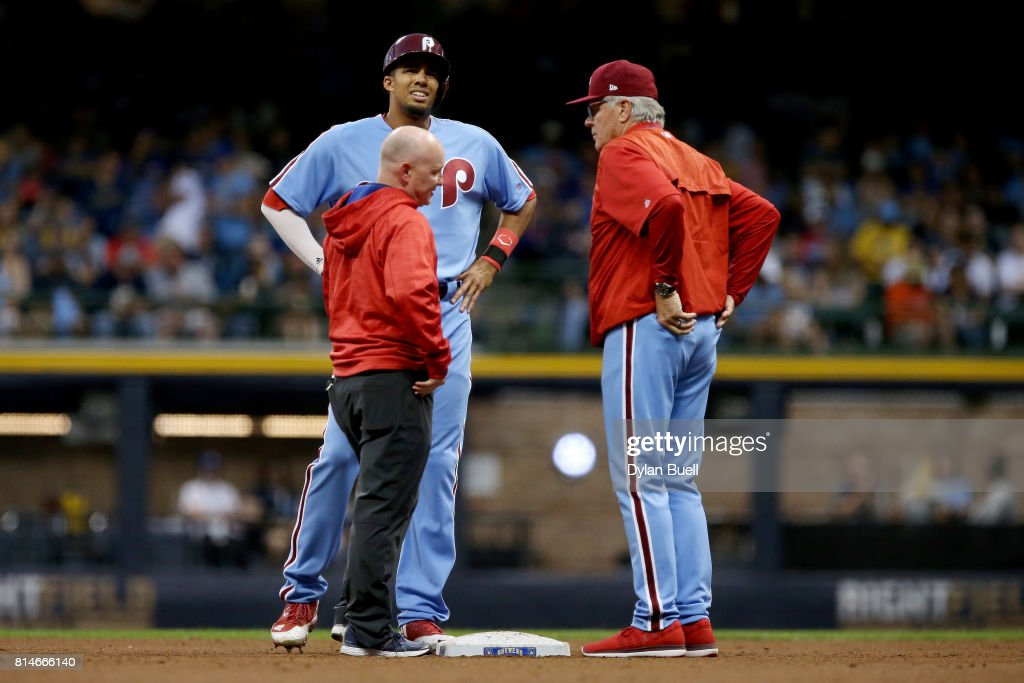 Aaron Altherr #23 of the Philadelphia Phillies is examined after being injured in the fifth inning against the Milwaukee Brewers at Miller Park on July 14, 2017 in Milwaukee, Wisconsin.