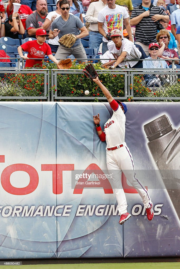 Aaron Altherr #40 of the Philadelphia Phillies is unable to catch a long fly ball hit by Chris Coghlan #8 of the Chicago Cubs who tripled in the first inning of the game at Citizens Bank Park on September 13, 2015 in Philadelphia, Pennsylvania.