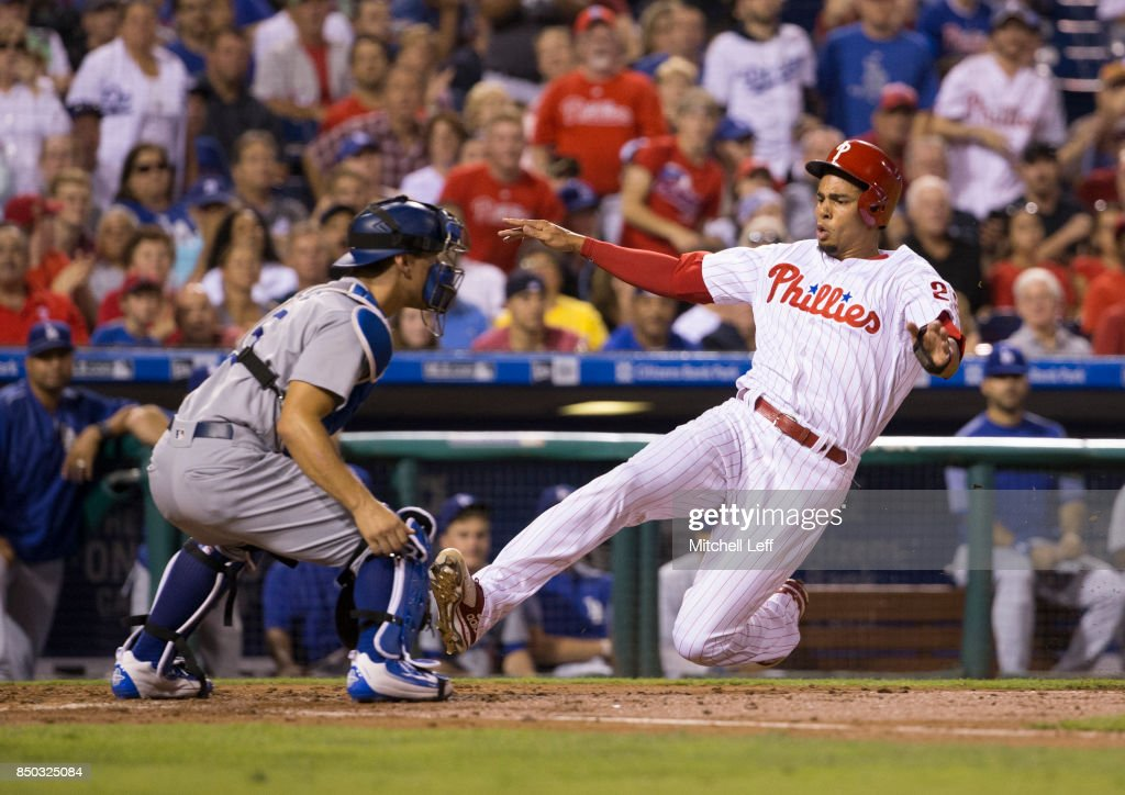 Aaron Altherr #23 of the Philadelphia Phillies slides past Austin Barnes #15 of the Los Angeles Dodgers to score a run in the bottom of the second inning at Citizens Bank Park on September 20, 2017 in Philadelphia, Pennsylvania.