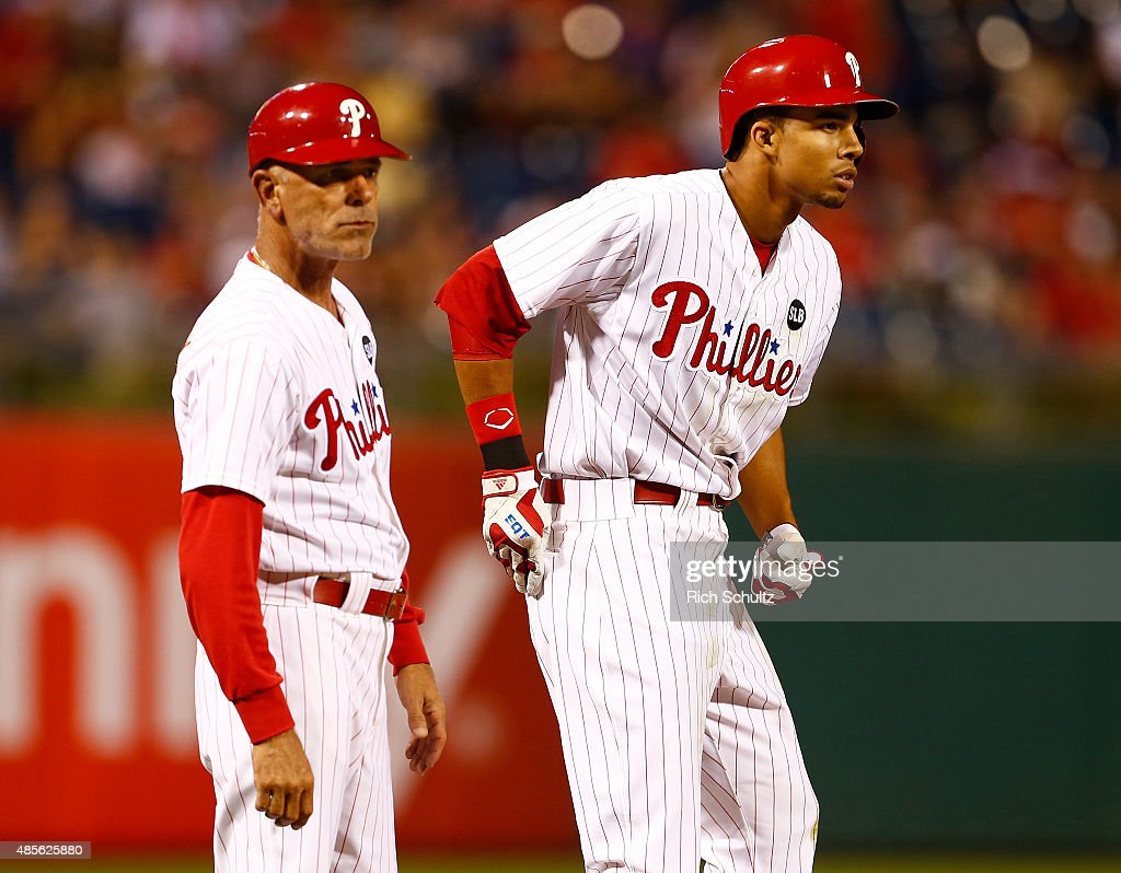 Aaron Altherr #40, right, of the Philadelphia Phillies is congratulated by third base coach John Mizerock #12 after hitting a triple in the seventh inning of a MLB game at Citizens Bank Park on August 28, 2015 in Philadelphia, Pennsylvania. The Phillies defeated the Padres 7-1.