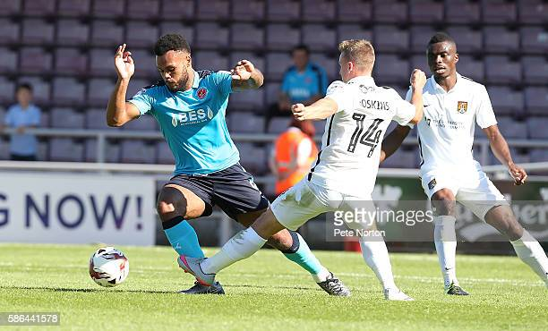 Aaron AmadiHolloway of Fleetwood Town moves away with the ball from Sam Hoskins of Northampton Town to head the ball during the Sky Bet League One...