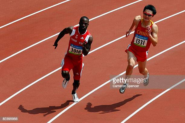 Aaron Armstrong of Trinidad and Tobago and Zhang Peimeng of China compete in the Men's 200m Heats at the National Stadium on Day 10 of the Beijing...