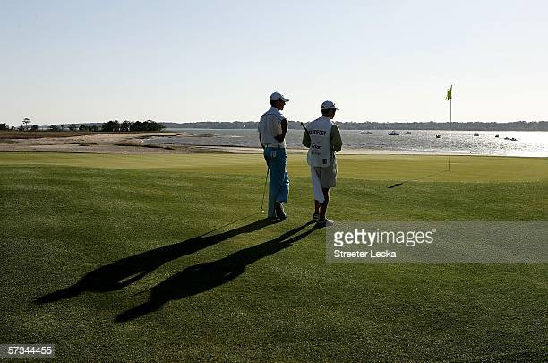 Aaron Baddeley of Australia and his caddie Kenny Harms watches on at the 18th hole during the third round of the Verizon Heritage at Harbour Town...