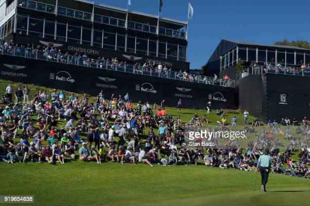 Aaron Baddeley of Australia far right tosses his golf ball into the gallery of fans after chipping it in on the 18th hole during the third round of...