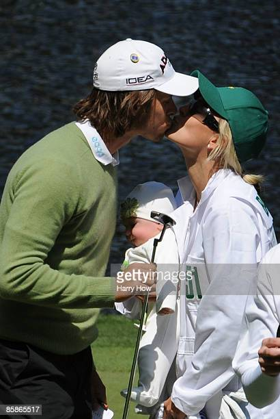 Aaron Baddeley of Australia kisses his wife Richelle on the ninth green during the Par 3 Contest prior to the 2009 Masters Tournament at Augusta...