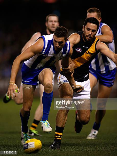 Aaron Black of the Kangaroos and Troy Chaplin of the Tigers compete for the ball during the round 15 AFL match between the North Melbourne Kangaroos...