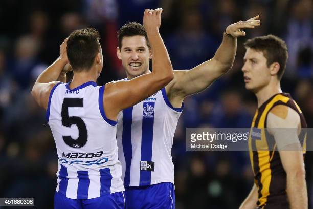 Aaron Black of the Kangaroos celebrates a goal with Ben Jacobs of the Kangaroos during the round 16 AFL match between North Melbourne Kangaroos and...