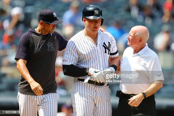 Aaron Boone of the New York Yankees attends to Luke Voit after being hit by a pitch in the fourth inning against the Colorado Rockies at Yankee...