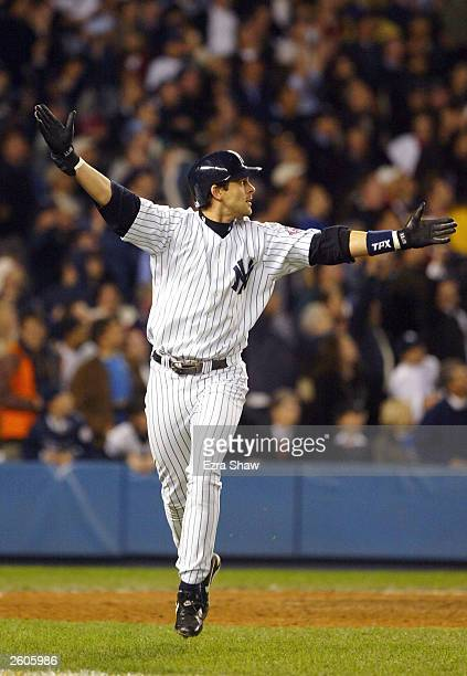 Aaron Boone of the New York Yankees celebrates after hitting the game-winning home run in the bottom of the eleventh inning against the Boston Red...