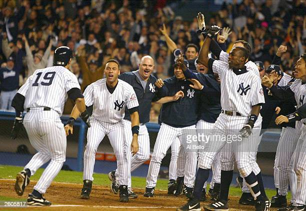Aaron Boone of the New York Yankees celebrates with his teammates after hitting the game winning home run in the bottom of the eleventh inning...