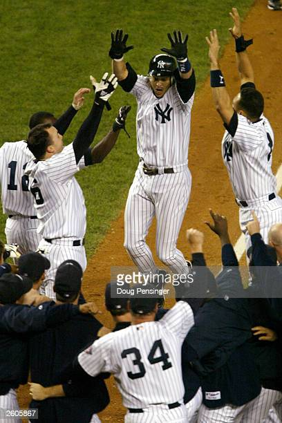 Aaron Boone of the New York Yankees is greeted by his teammates at home plate after a he hit the game winning homerun in the 11th inning off of Tim...