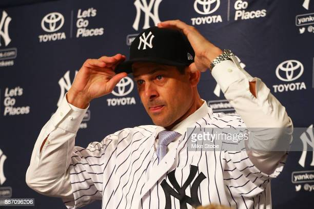 Aaron Boone puts on a Yankee cap after being introduced as manager of the New York Yankees at Yankee Stadium on December 6 2017 in the Bronx borough...