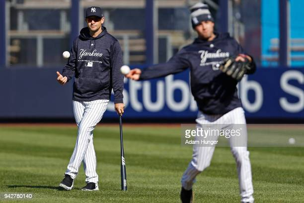Aaron Boone watches as Tyler Wade of the New York Yankees throws during batting practice prior to taking on the Baltimore Orioles at Yankee Stadium...